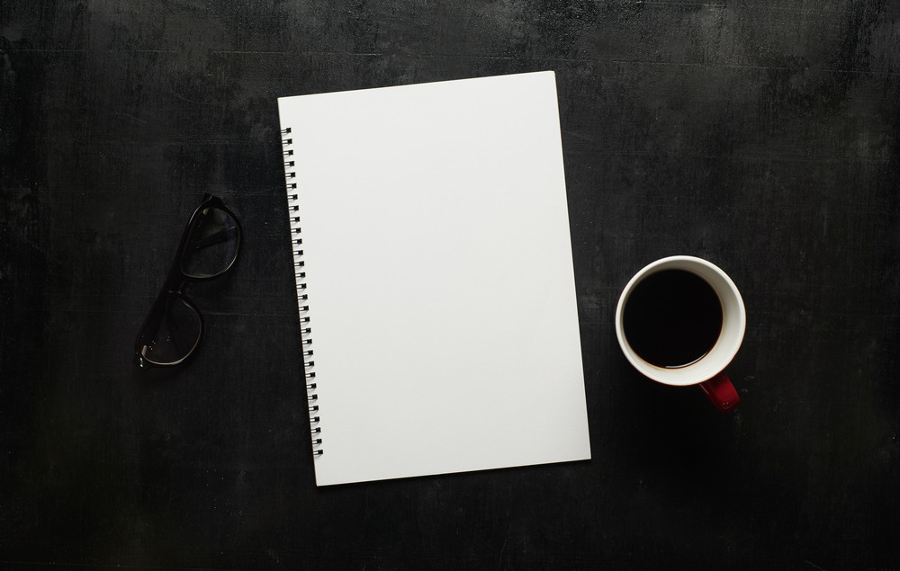 Wooden black office desk table with notebook, eyeglasses and  cup of coffee. Blank notebook page for input the text in the middle. Top view