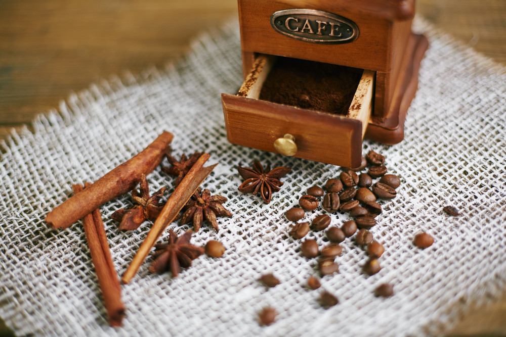 Wooden coffee grinder with coffee powder and aromatic grains, star anise and cinnamon sticks near by