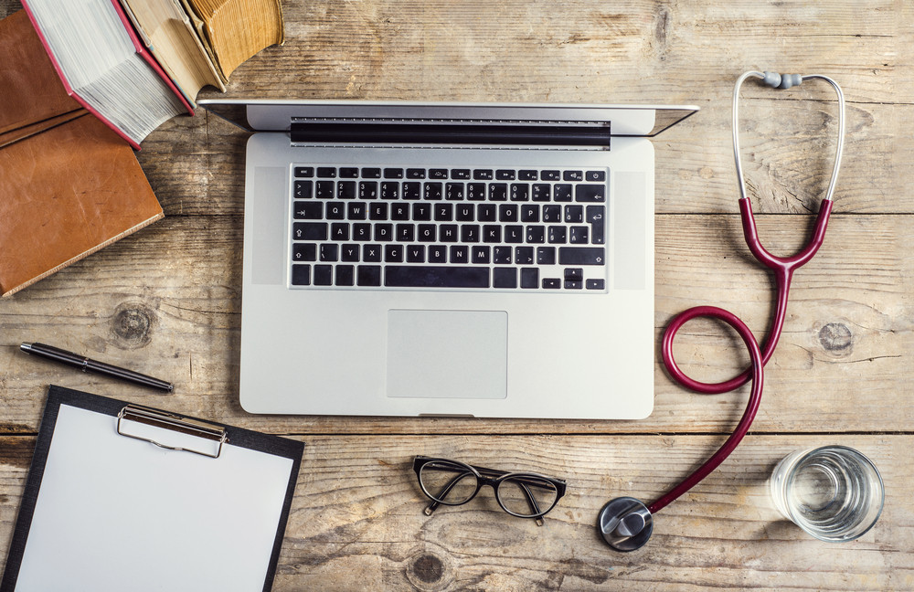Workplace of a doctor. Stethoscope, notebook, clip board, glasses and other things on wooden desk background.