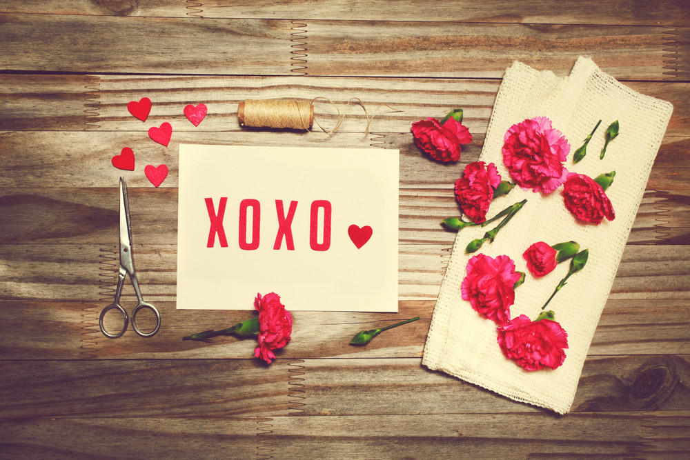 Xoxo love theme with scissors, twine, and carnation flowers on grungy background