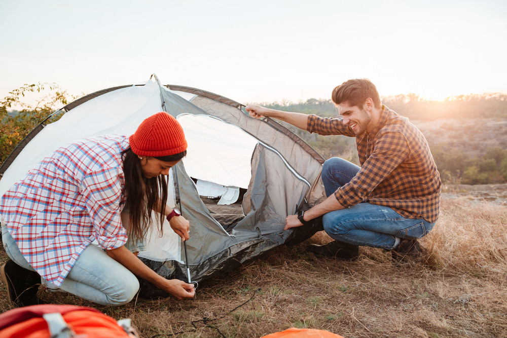 Young active couple setting up a tent outdoors