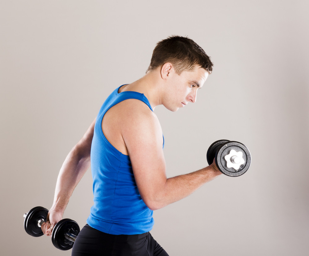 Young active man with barbell is training in studio