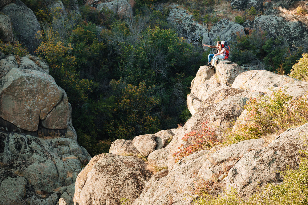 Young adventure couple sits on rock