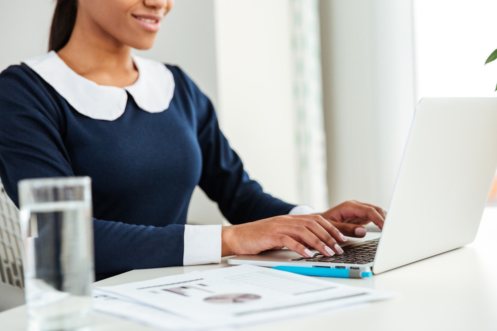 Young african business woman in dress sitting by the table on workplace with water and using laptop. Cropped image