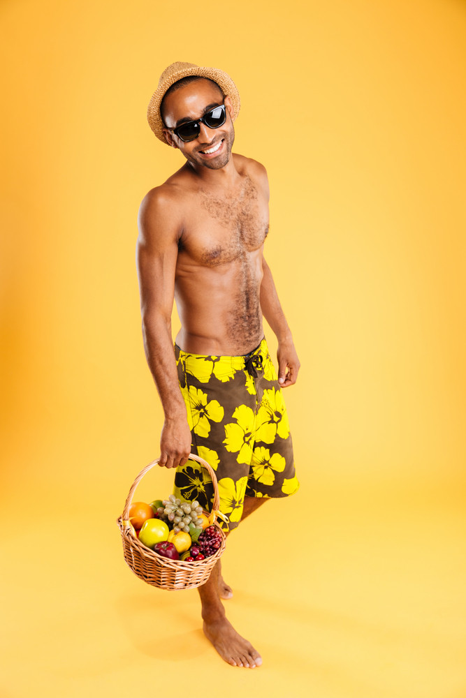 Young afro american man holding fruit basket isolated on a orange background