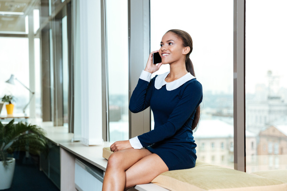 Young afro business woman in dress sitting near the window and talking on phone in office. Side view