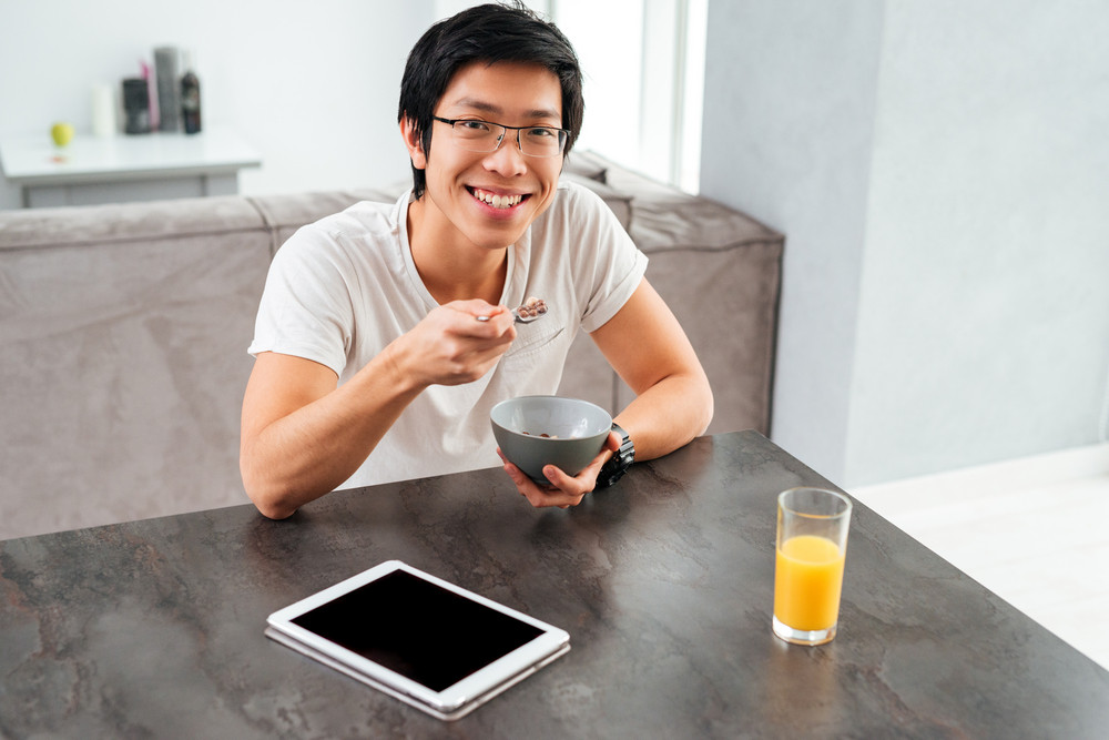 Young asian man with cereal. sitting by the table. with tablet and juice. looking at cabera
