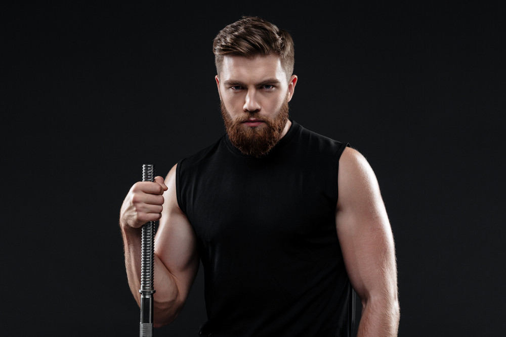 Young athletic man with barbell. so serious. isolated dark background
