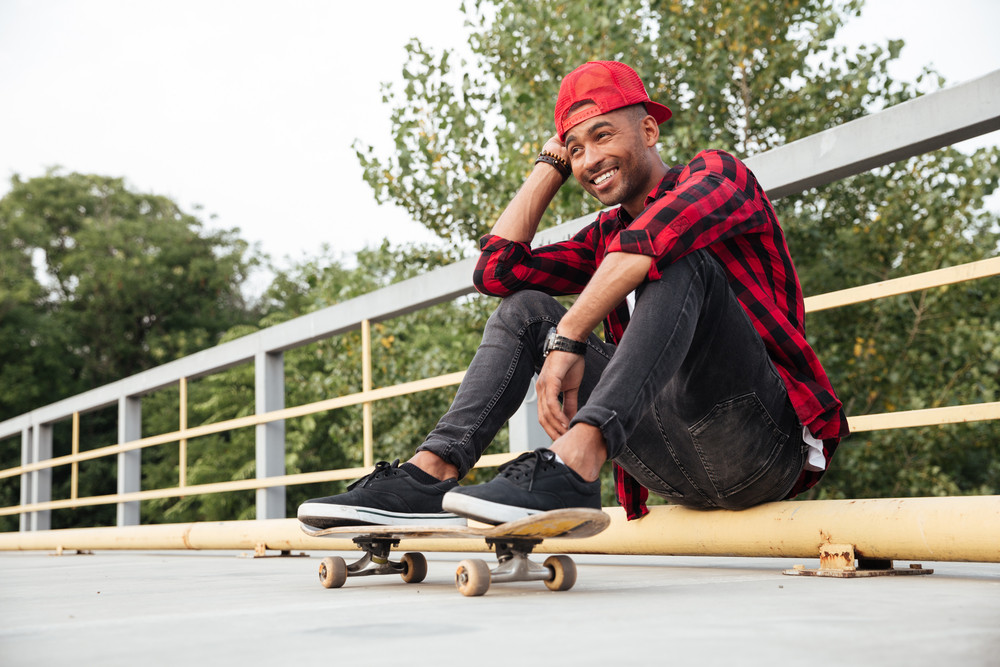 Young attractive dark skinned man sitting with his skateboard. Against nature background.