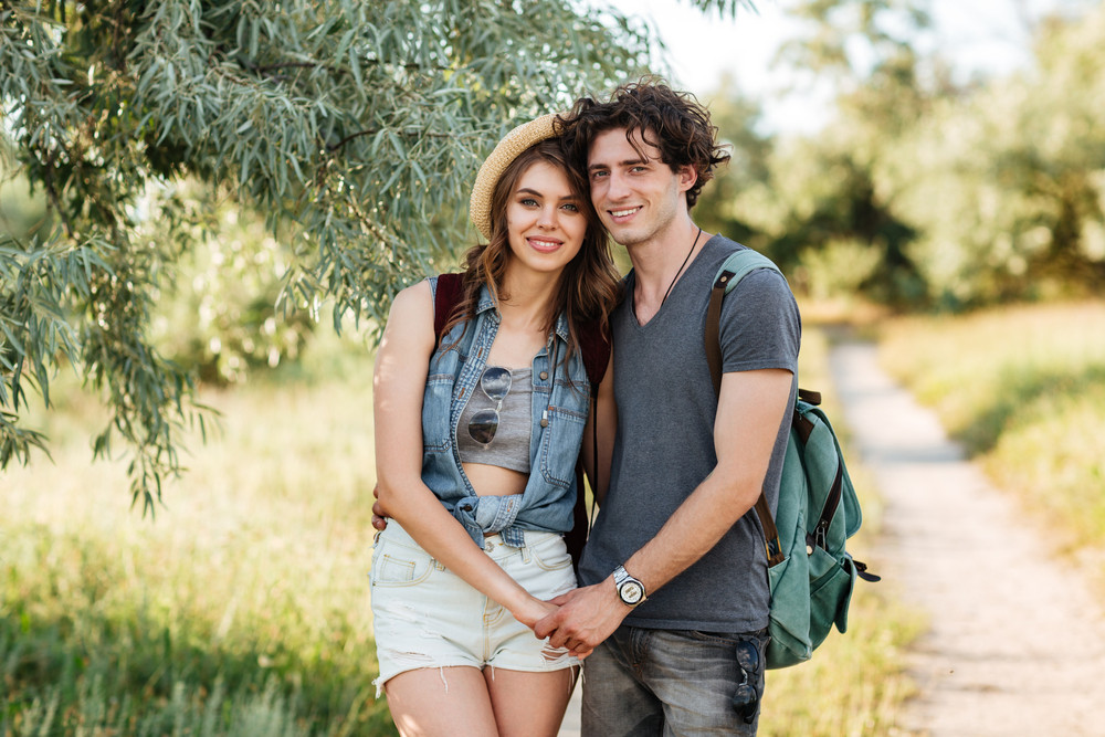 Young attractive hipster couple standing against trees on the background and holding hands