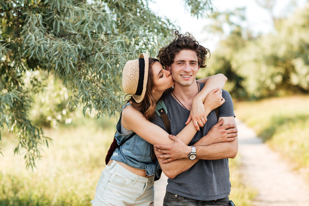 Young attractive hipster couple standing against trees on the background kissing and hugging