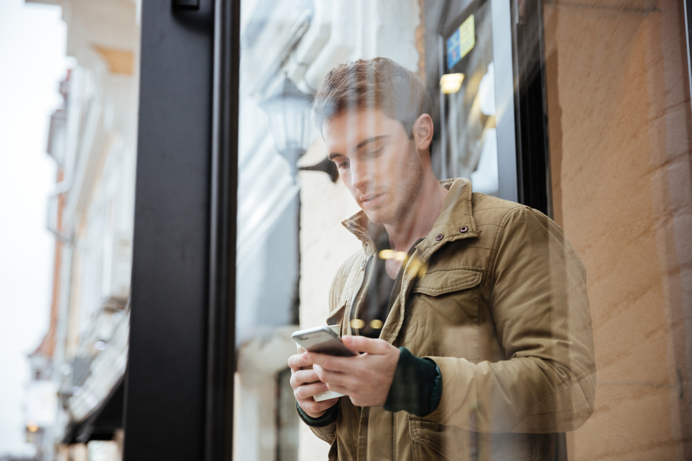 Young attractive man walking on the street and chatting by his phone outdoors. Look at phone.