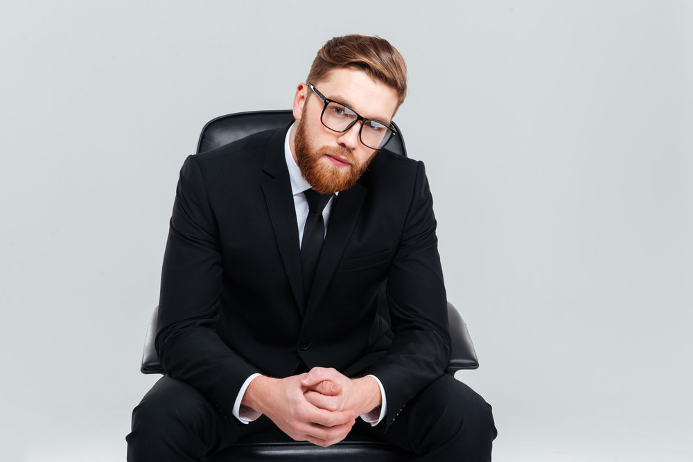 Young bearded business man in glasses and black suit sitting on armchair and looking at camera