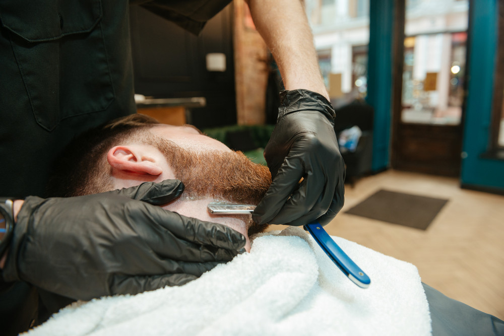 Young bearded man getting beard shaving by hairdresser while lies in chair at barbershop.