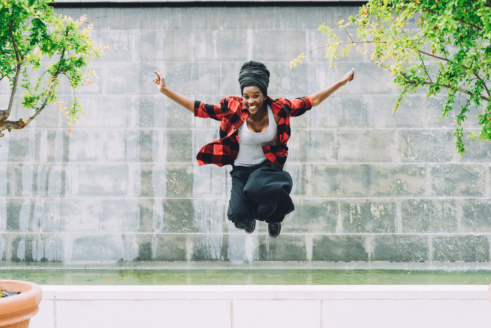 Young beautiful afro black woman jumping in the air outdoor in the city, looking at camera laughing - enjoyment, freedom, playful concept