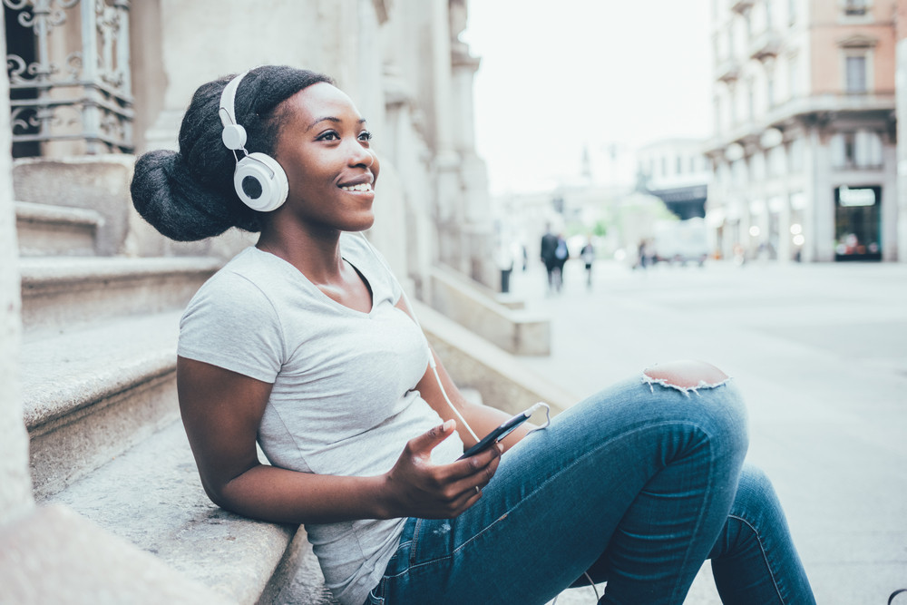 Young beautiful afro black woman outdoor in the city sitting on the ground, listening music with headphones and smart phone hand hold, overlooking smiling - happiness, relaxing, carefree concept