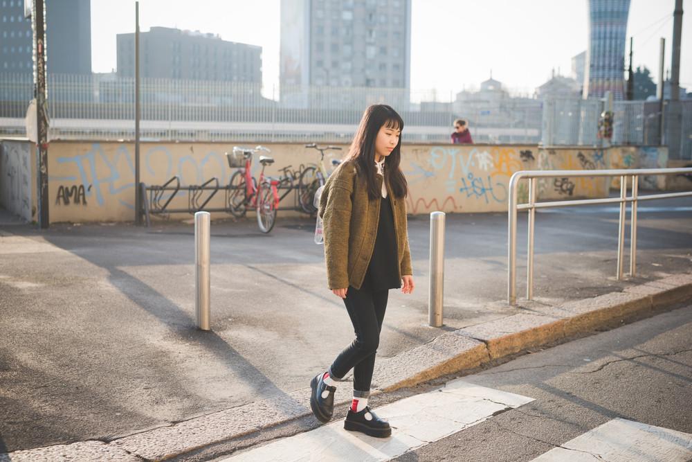 young beautiful asian hipster woman in the city - walking the street crosswalk having fun