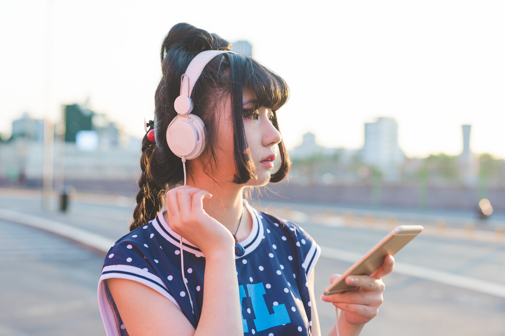 Young beautiful asian nonconformist woman listening music with headphones and smart phone hand hold outdoor in city back light, tapping the touchscreen - music, technology, social network concept