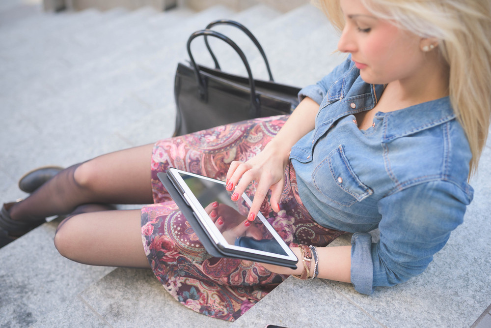 Young beautiful blonde caucasian girl seated on a staircase using a tablet looking downward the screen - communication, technology, social network concept