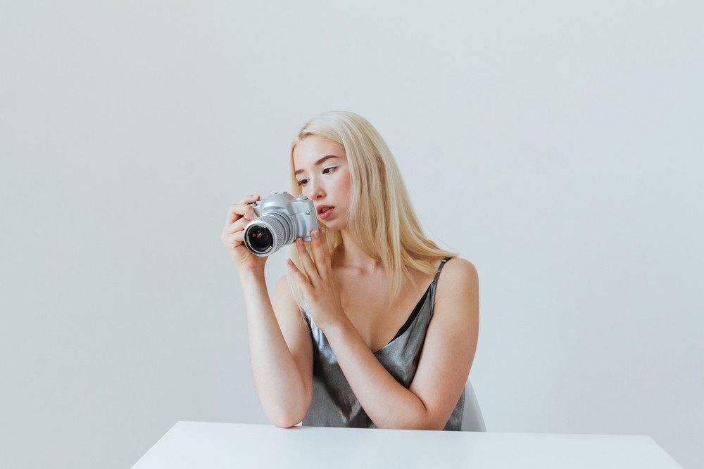 Young beautiful blonde girl in silver dress looking at camera lens and sitting at white table isolated on the grey background