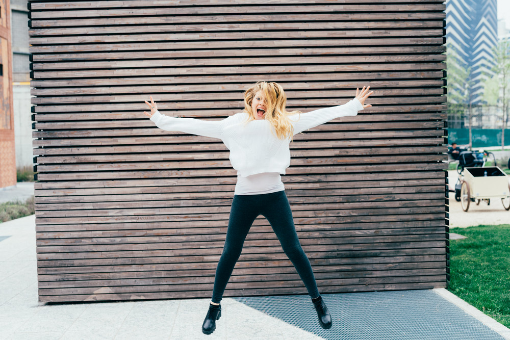 Young beautiful blonde woman jumping outdoor in the city - girl power, satisfaction, goal concept