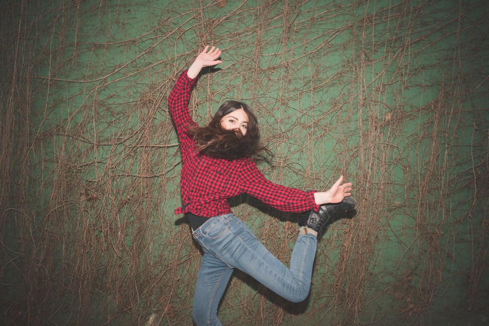 Young beautiful brunette long hair girl posing in front of a green wall touching her hair dressed with checked red shirt, blue jeans and black shoes. Light obtained due to the use of a flash