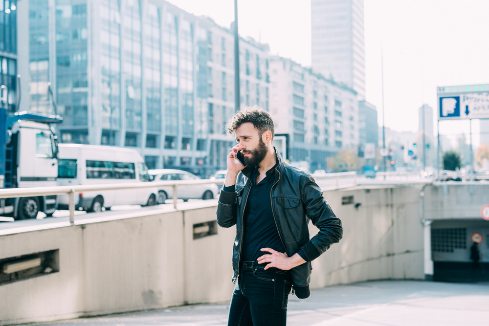 Young beautiful caucasian bearded man walking outdoor in the city talking smart phone - business, conversation, communication concept
