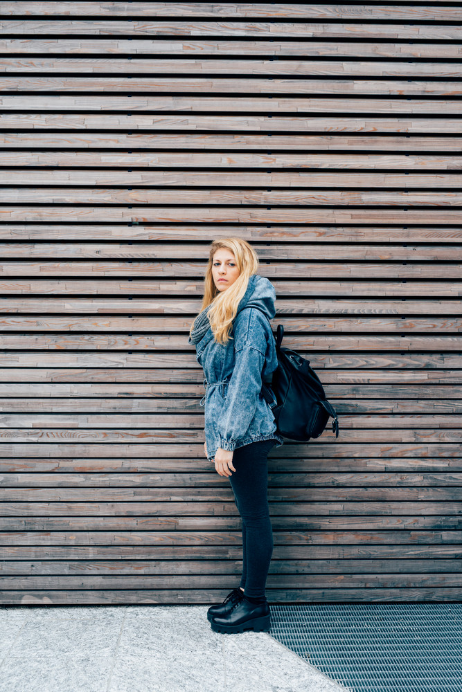 Young beautiful caucasian blonde girl outdoor in the city wearing backpack, looking at camera, serious - pensive, thoughtful, thinking future concept