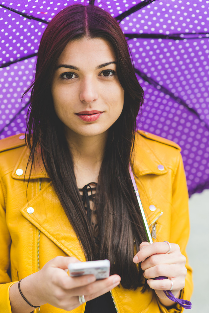 Young beautiful caucasian brown hair woman holding purple weather and smart phone, looking at cmera smiling - technology, social network, weather concept