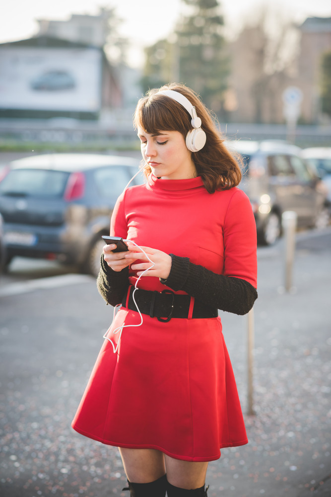 Young beautiful caucasian hipster woman outdoor in the city listening music with headphones and smart phone hand hold - music, playlist, technology concept