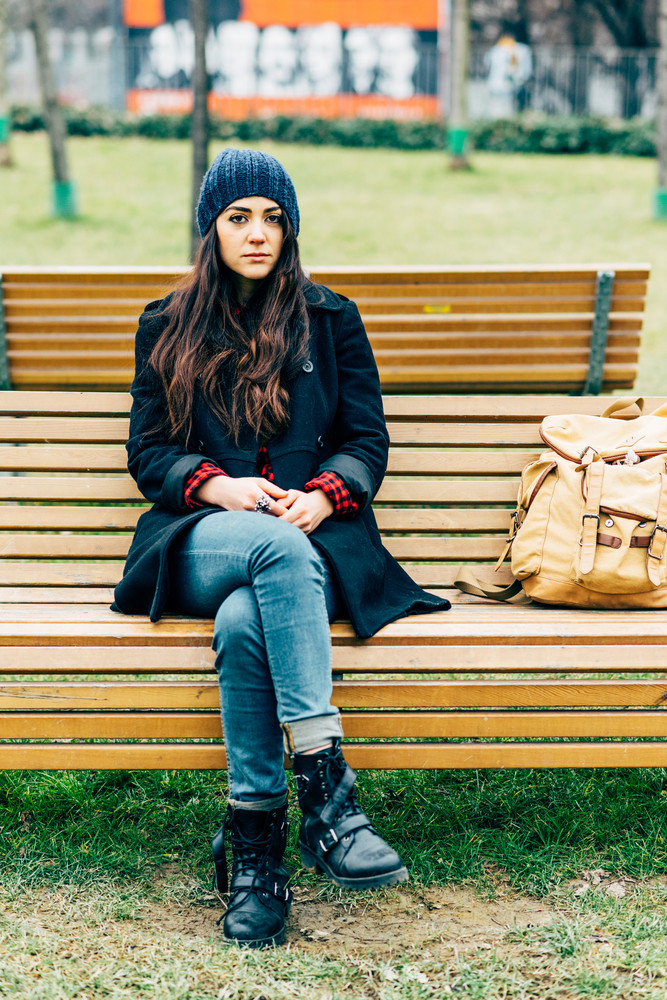 Young beautiful caucasian long brown hair woman sitting outdoor in a city park on a bench, looking at camera, pensive - thoughtful, thinking future, serious concept