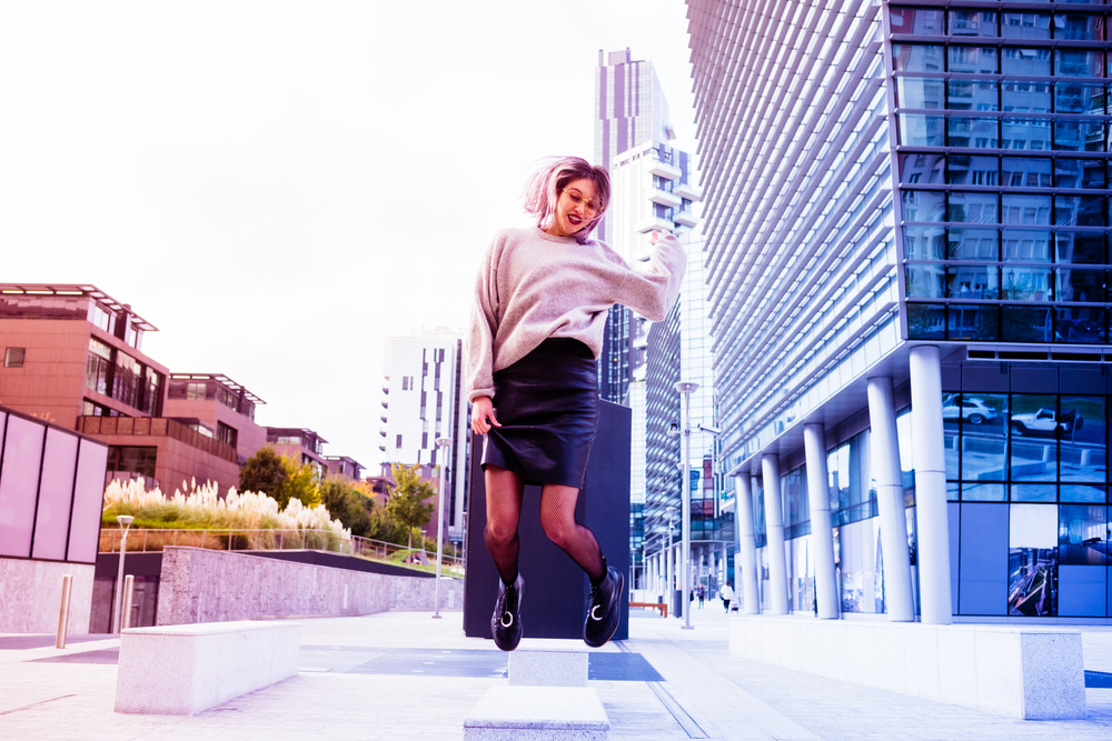 Young beautiful caucasian purple grey hair woman jumping outdoor in the city in back light - happiness, satisfaction, succesful concept