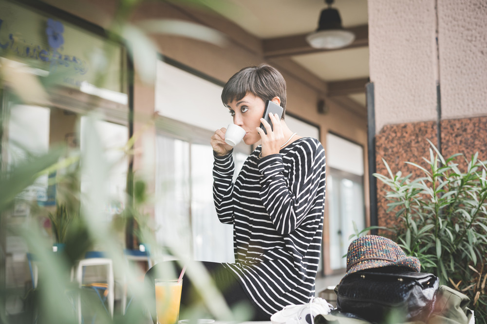 Young beautiful caucasian short hair woman having a coffee talking smart phone - communication, technology, call concept