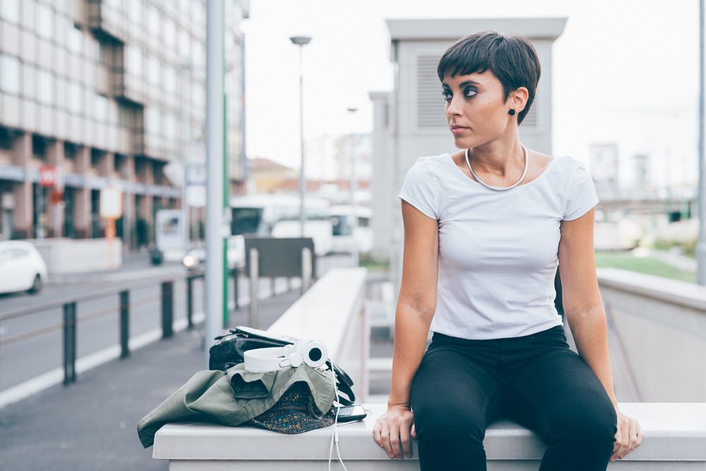 Young beautiful caucasian woman sitting on a small wall outdoor in the city, overlooking pensive, with smart phone and headphones next to her - serious, pensive, thoughtful concept