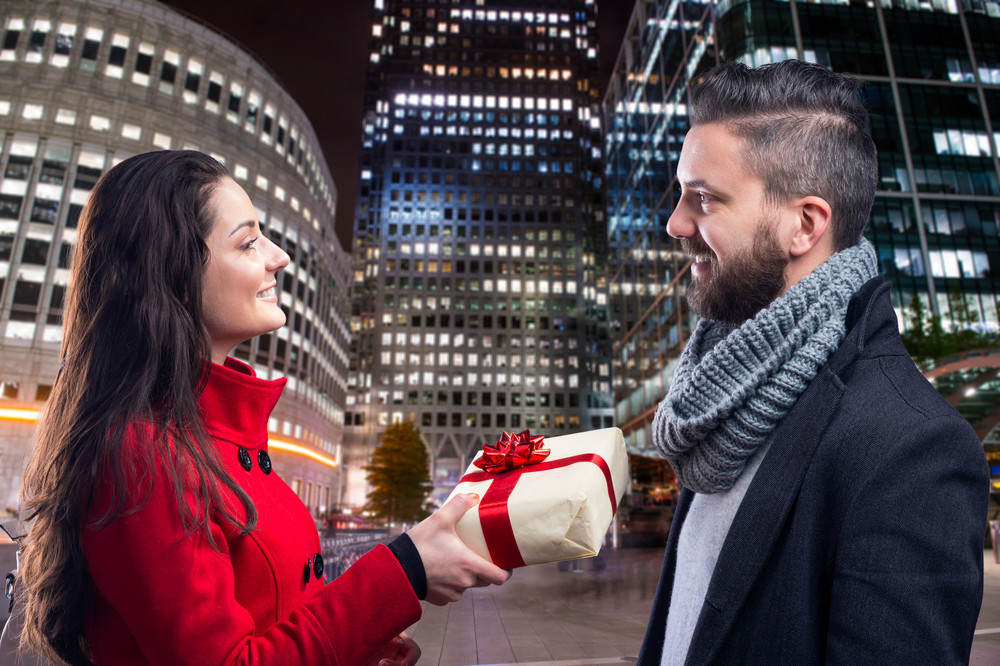 Young beautiful couple buying gifts in the city
