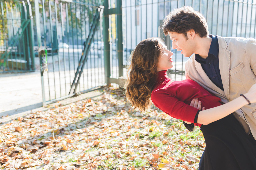 Young beautiful couple in love dancing outdoor in the city back light - love, romantic, dancing concept