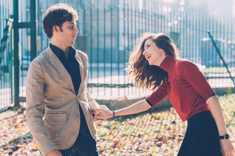 Young beautiful couple in love having fun outdoor in back light - happiness, romance, togetherness concept