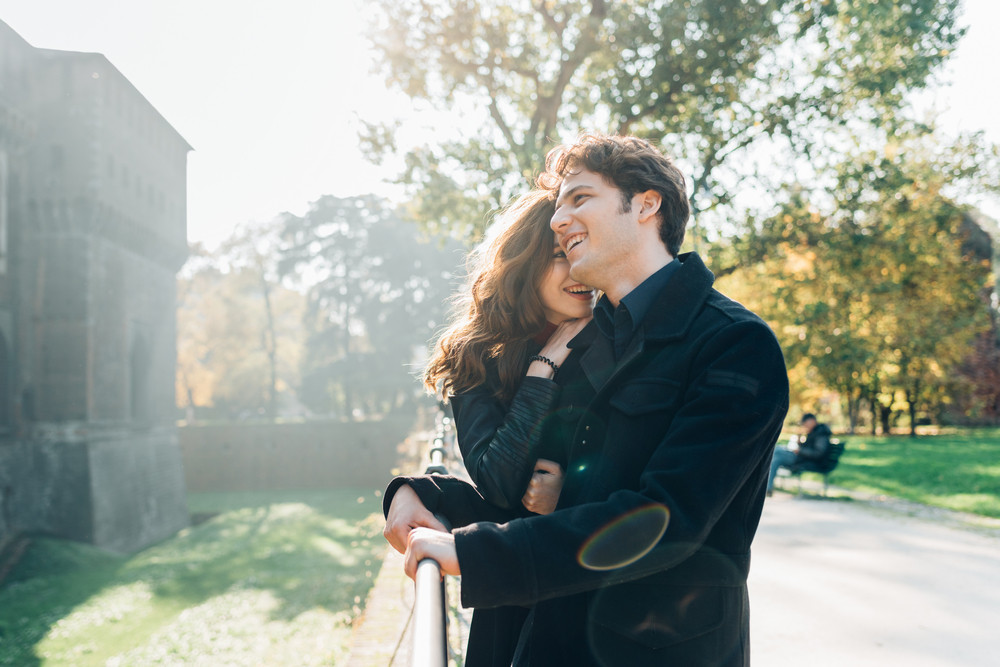 Young beautiful couple in love having fun outdoor in back light, hugging - happiness, romance, togetherness concept