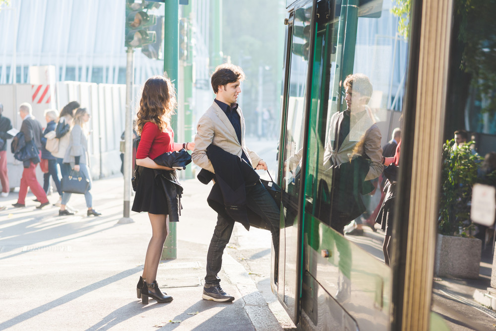 Young beautiful couple in love taking tram outdoor in the city - commmuter, transport concept