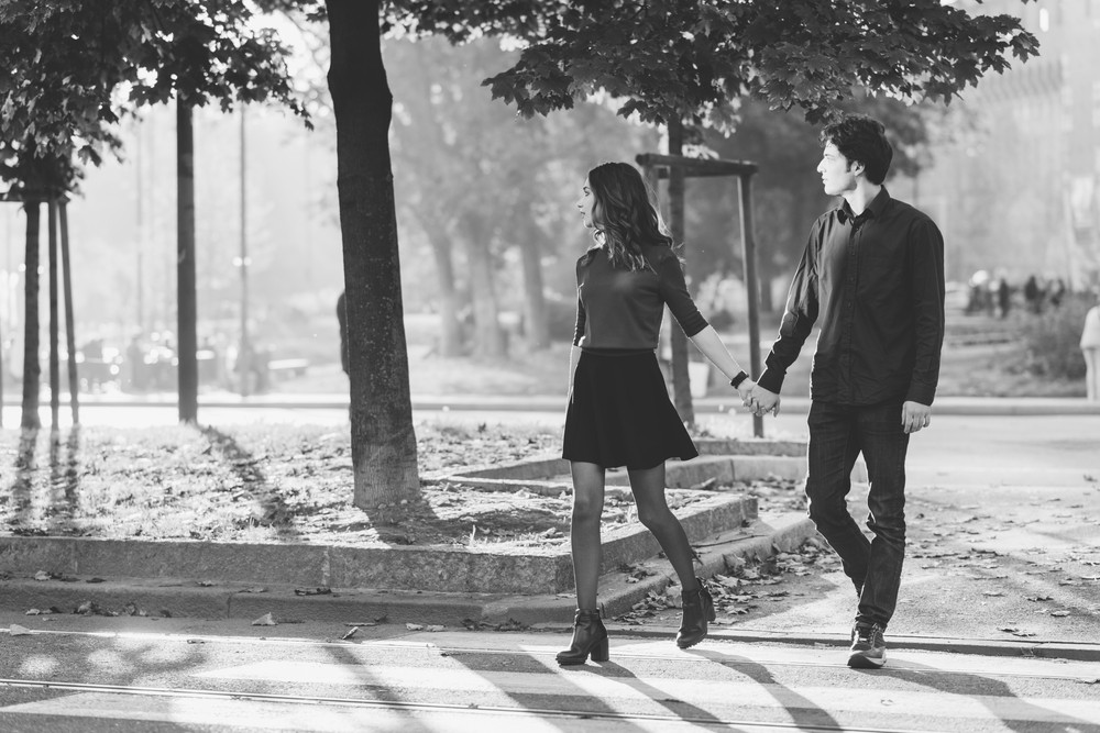 Young beautiful couple in love walking hand in hand in the city - first date, romantic, love concept - black and white filter