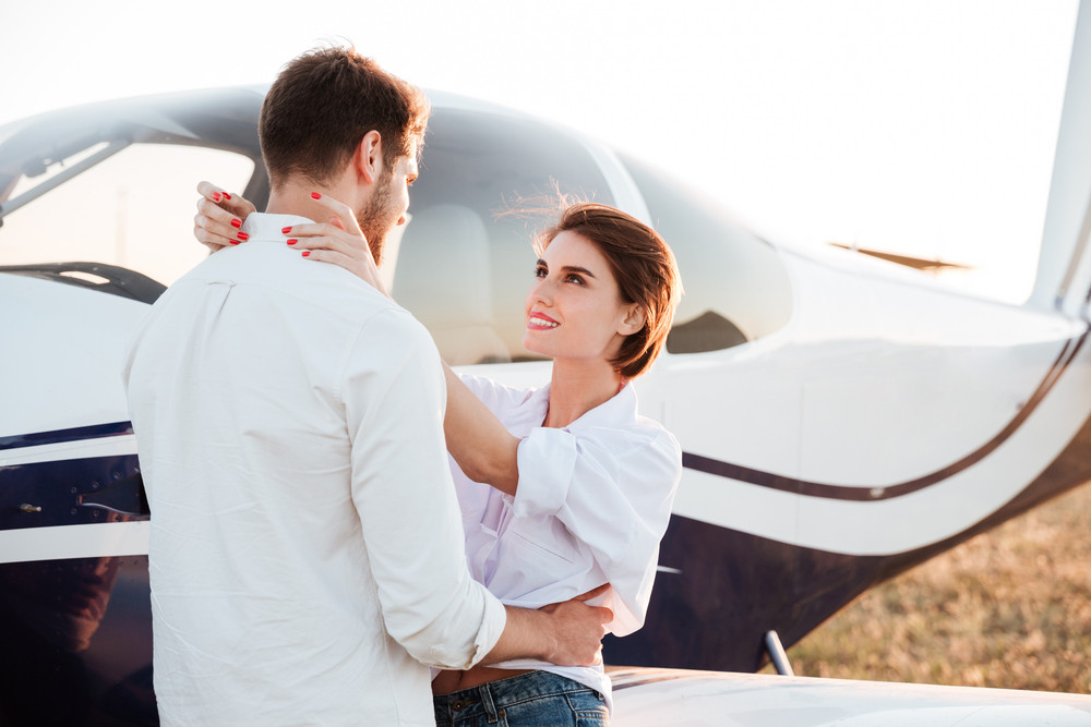 Young beautiful couple together with airplane on background during sunset
