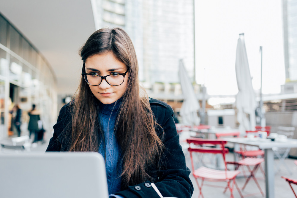 Young beautiful eastern business woman outdoor in the city sitting bar using computer - business, work, technology concept