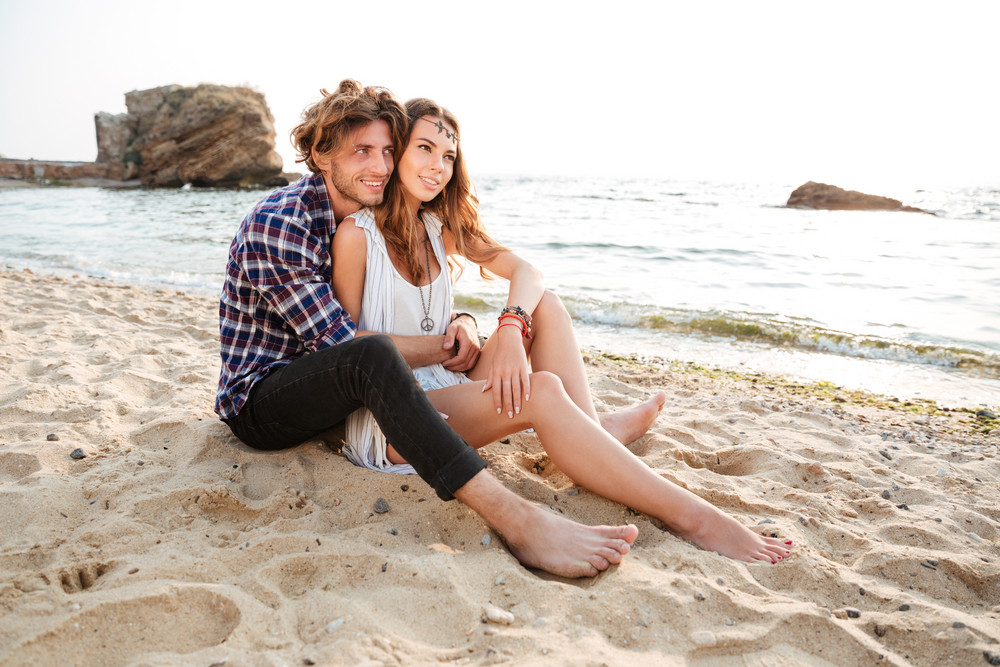 Young beautiful happy couple in love embracing while sitting at the beach