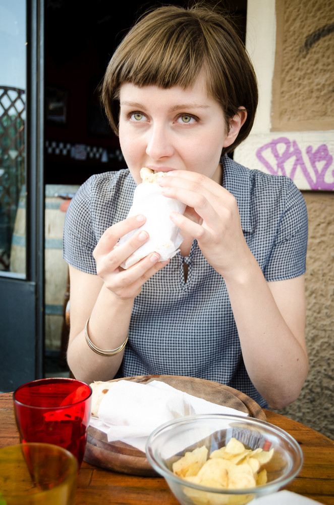 young beautiful hipster woman eating at the bar