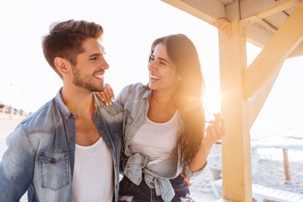 Young beautiful laughing couple looking at each other standing at the beach