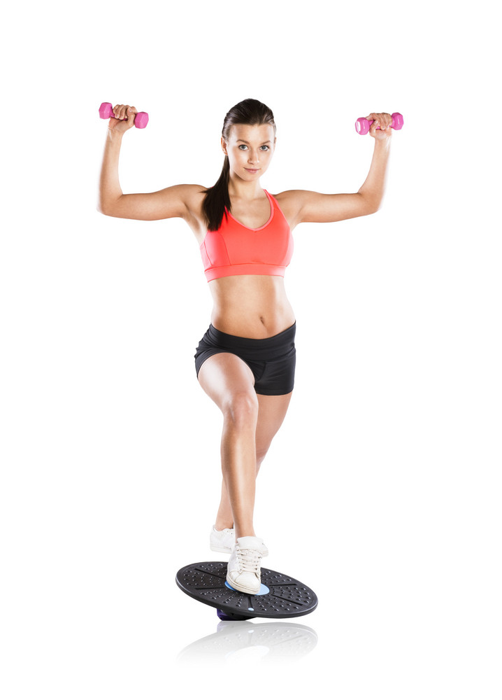 Young beautiful model with fitness balance board