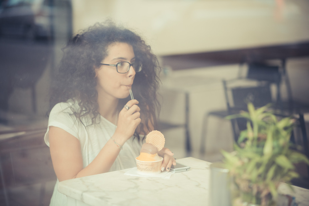 young beautiful moroccan curly woman using smartphone at the bar
