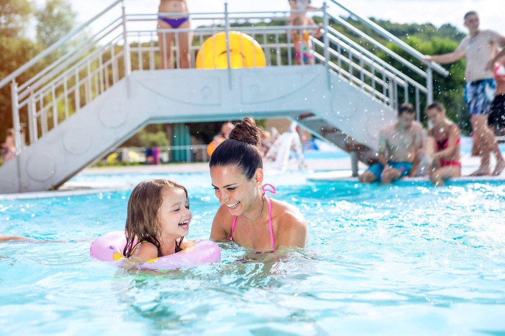 Young beautiful mother in bikini playing with her daughter in inflatable ring in swimming pool in aqua park. Summer heat and water.