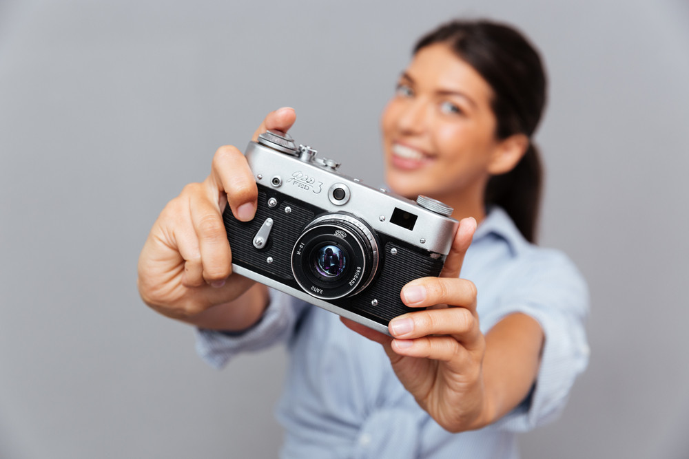 Young beautiful smiling brunette woman showing photo camera isolated on a gray background