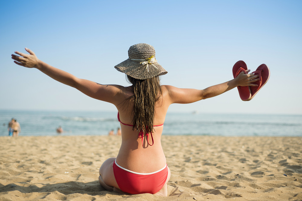 Young beautiful woman in sunhat relax on the summer beach.